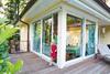Kind durch offene Schiebeglastuer zur Terrasse