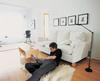 Mann mit Laptop am Wohnzimmerboden
