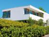 Weißes Haus mit Flachdach und breiten Balkon