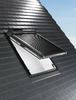 Schwarzes Hausdach mit offenem Dachfenster