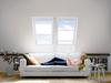 Lesende Frau auf Couch unter zwei Dachfenstern