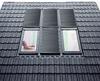 Schwarzes Hausdach mit Solarsystem und Dachfenster