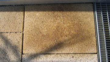 Naturstein-Beschädigung durch rostigen Splitt im Untergrund
