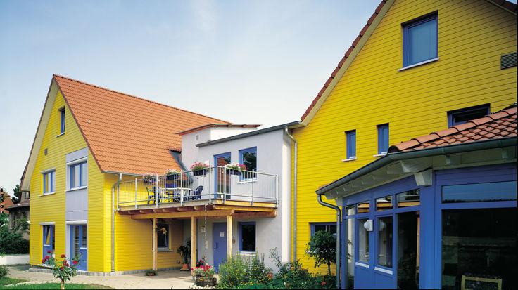 Haeuserverbund mit gelber Fassade und blauen Fenstern