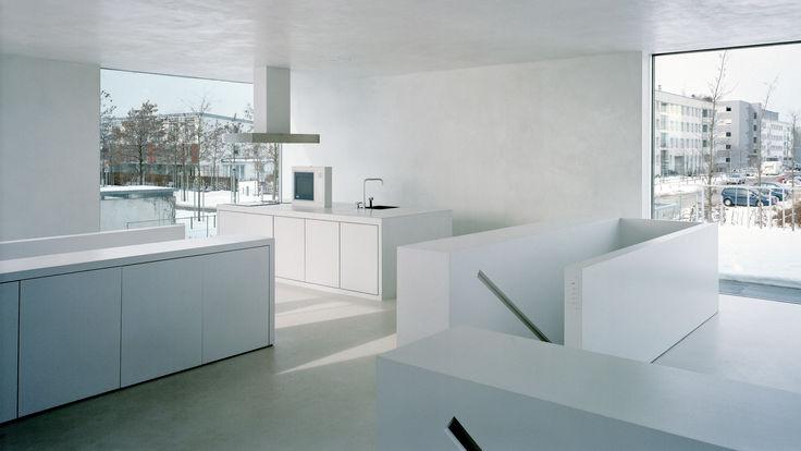 Großer weißer Leerraum mit Treppenaufgang und Kueche