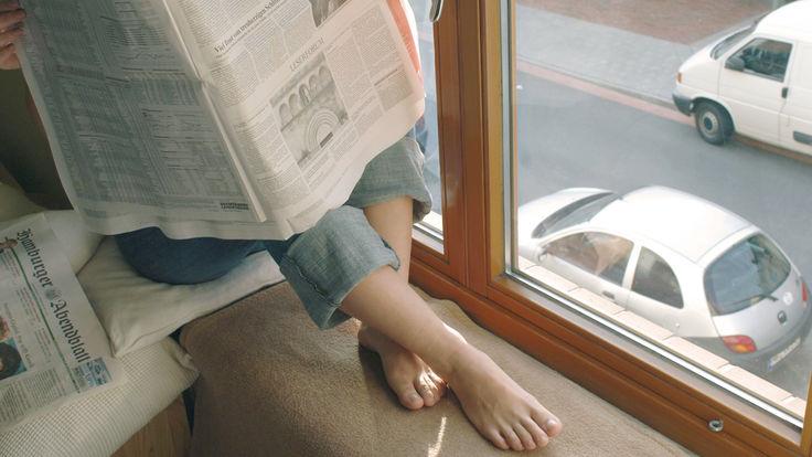 Zeitung lesen am Fenster zur Straße