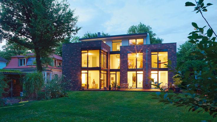 Haus mit hell beleuchteter Fensterfront und Falttueren