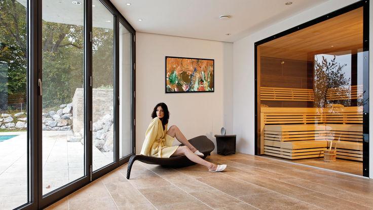 Frau im Saunamantel sieht aus dem Fenster