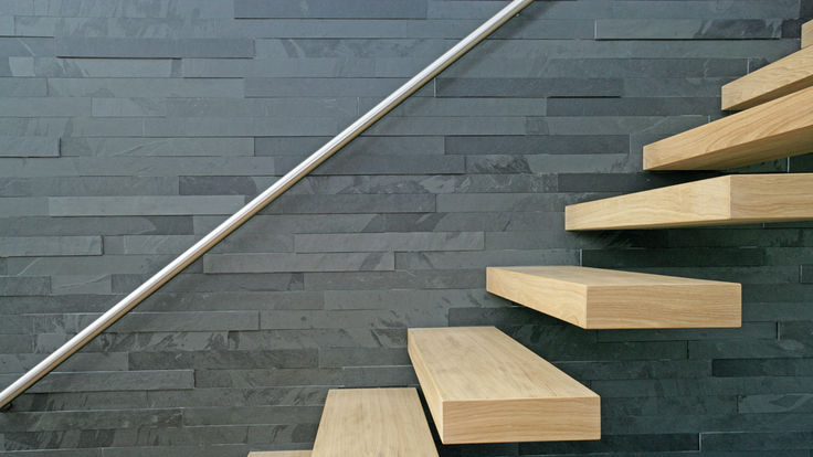 Schieferstein anthrazit hinter Holztreppe