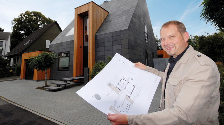 Mann mit Bauskizze vor einem Haus
