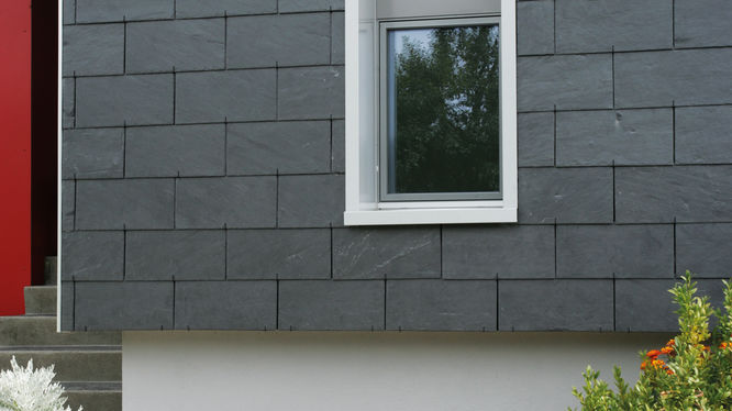 Haus mit grauer Steinfassade und weißem Fenster
