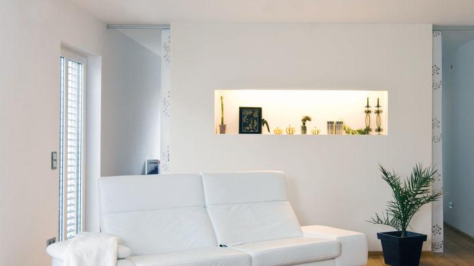 Weiße Couch vor beleuchteter Wandnische