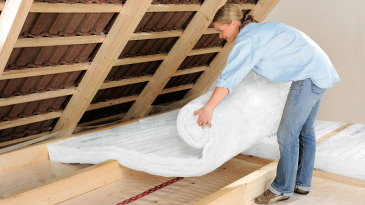 Frau verlegt Daemmmatten am Dachboden