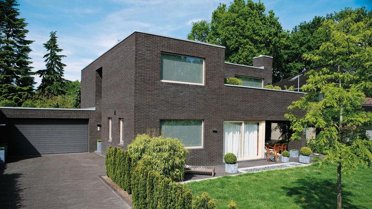 Haus mit Flachdach und dunkler Mauerwerksfassade