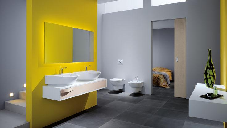 Gelbe Wand mit Doppelwaschbecken und großen Spiegel