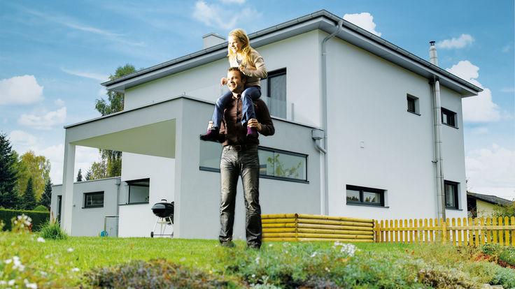 Vater mit Kind auf Wiese vor weißem Haus