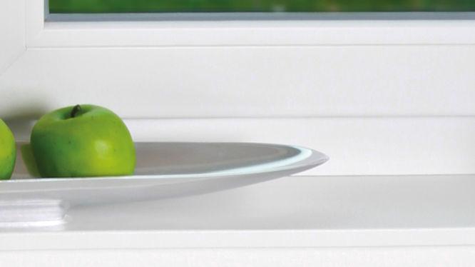 Teller mit grünen Äpfeln am Fenstersims