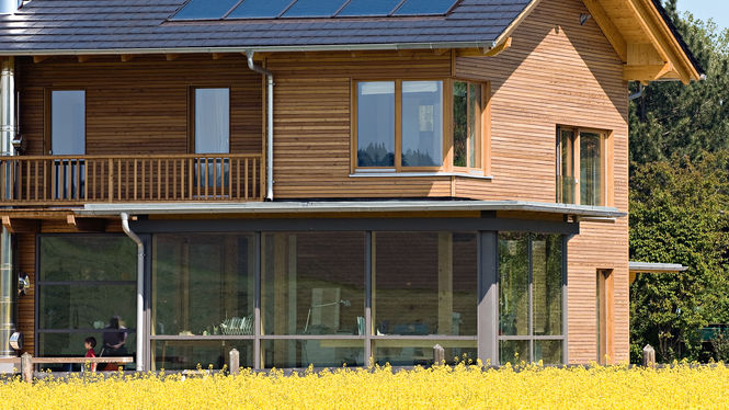 Holzhaus mit Solaranlage am Feldrand