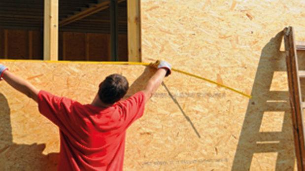 Abmessender Handwerker vor Grobspanplatten-Hauswand