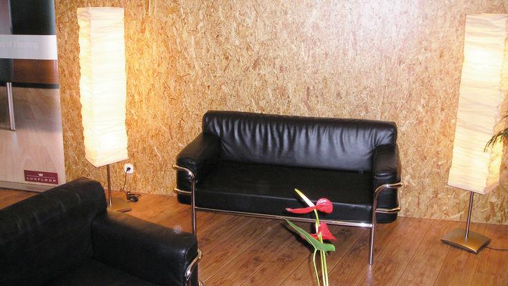 Schwarze Couch vor Spanplattenwand