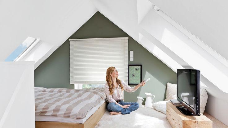 Sitzende Frau mit Fernbedienung im Dachzimmer