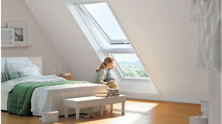 Sitzende Frau blickt aus dem Dachfenster