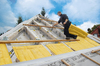 Arbeiter verlegt Daemmfilze am Hausdach