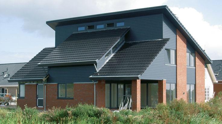Haus mit roter Fassade und dunkelgrauem Ziegeldach