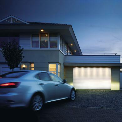 Auto vor Haus und Garage bei Abenddaemmerung