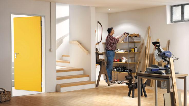 Arbeitsraum im Keller mit Treppenaufgang und gelber Tuer