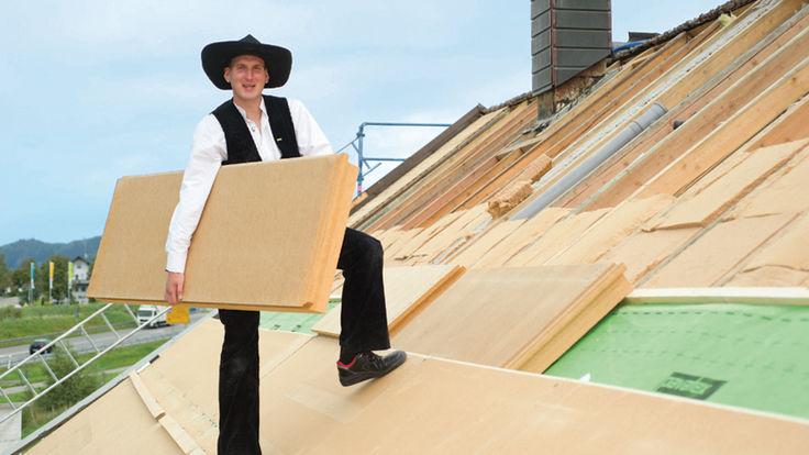 Mann mit Holzfaser-Dämmplatte am Hausdach