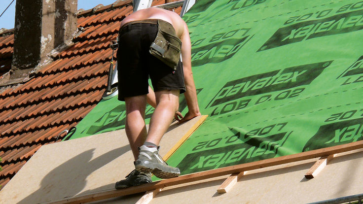 Dachdecker verlegt Holzfaser-Daemmplatte an der Dachschraege